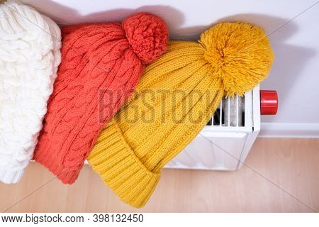 Colorful Winter Knitted Caps, Hats Hanging And Drying On A Hot Central Heating Radiator, Winter Fami