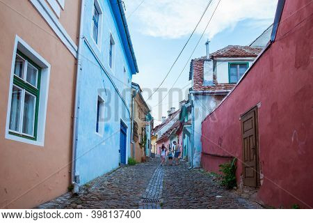 Sighisoara, Romania - August, 2019: Streetlife. Old Medieval Cobblestone Street With Colorful Houses