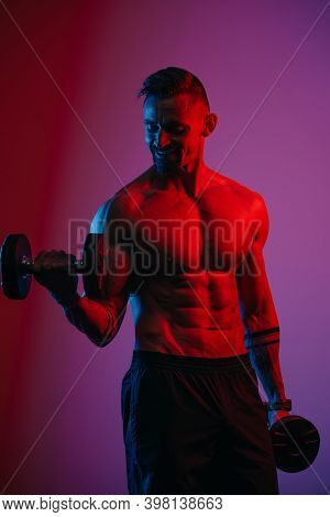 A Muscular Man With A Beard Who Is Doing Bicep Curls With Dumbbells Under Blue And Red Lights. An At