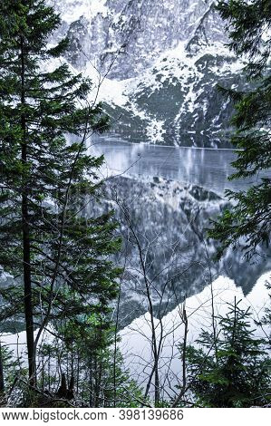 Beautiful Mountains Covered With Snow Reflect In Lake, Winter Time. Pine Trees, Green, Blue And Whit