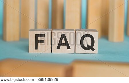 Faq Frequently Asked Questions Abbreviation Written On Wooden Blocks On A Blue Background.