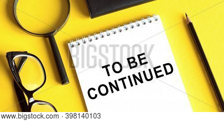 Notepad With The Text To Be Continued On A Yellow Background With Glasses, A Magnifying Glass And A