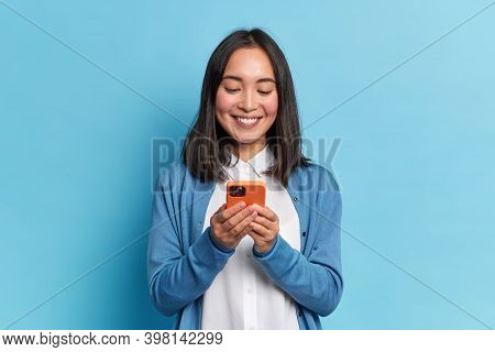 Smiling Charming Brunette Asian Woman Uses Mobile Phone Happy Texting In Social Networks Addicted To