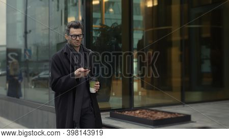 Man In Black Coat And Eyeglasses Looking At The Phone Walking Along The Street With Coffee, Slow Mot