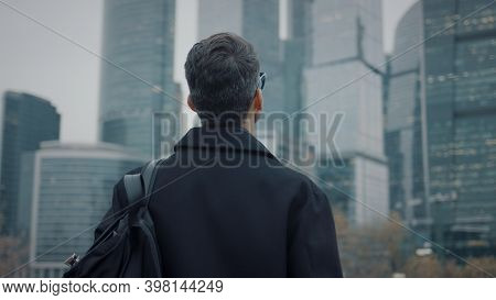 Man In Coat Looking At The Skyscrapers Pan Shot Right To Left. Gimbal Back Shot Of Businessman In Ey