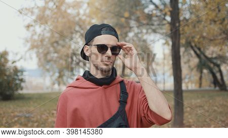 Man Runner Put Off Eyeglasses And Put On Earbuds Getting Ready For Run In A City Park. Runner In Red