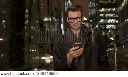 Man In Eyeglasses With Phone In Hand On Background Of Building With Lights On. Handheld Night Shot O