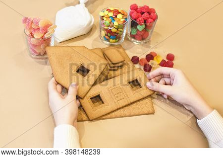 A Womans Hands,  Going To Decorate  A Christmas Gingerbread House With White Frosting Icing Cream To
