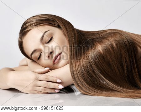 Portrait Of Young Pretty Woman Model With Silky Long Straight Hair Lying And Relaxing With Eyes Clos