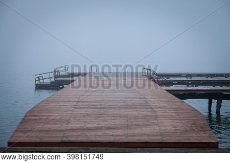 Pontoon On The Palic Lake Near Subotica, Serbia, With Grey Waters In Autumn And A Heavy And Mysterio