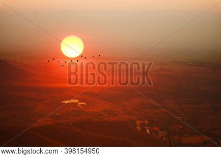 Sunset On Evening Sky Over Mountain And Silhouette Bird Flying Over Country