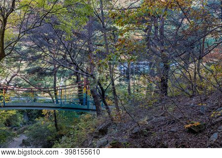 Metal Footbridge Over Ravine In Mountain Forest.
