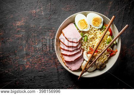 Instant Noodles With Vegetables, Egg, Mushrooms And Slices Of Becon. On Dark Rustic Background