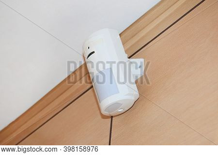 Motion Sensor Of The Security Alarm System. A White Volume Sensor Hangs On The Wall In A Room Or Off