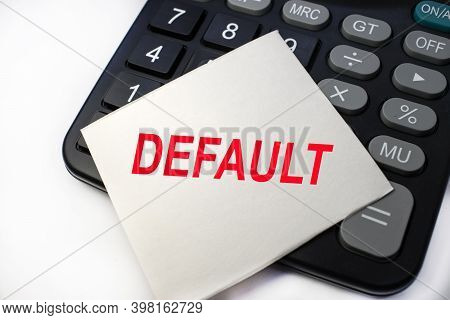 The Default Is Written On A White Sheet Of Paper, Which Is Located On A Black Calculator. Business C
