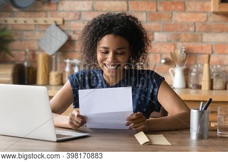 Emotional Young Positive African Ethnicity Woman Reading Paper Correspondence.