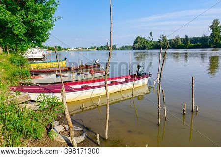 Fishing Boats Are Anchored On Improvised Dock On The River, Settlement In The Distance.