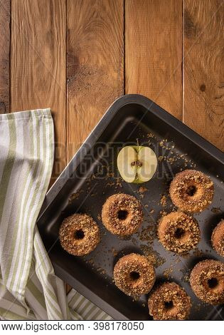 Homemade Baked Apple Cider Donuts On Baking Tray, Textile Napkin And Apple On Wooden Table. Ready To