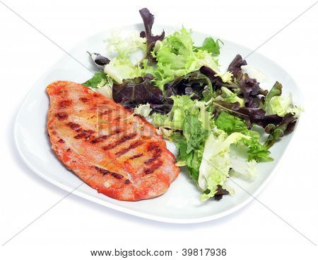 a plate with grilled chicken and green salad on a white background