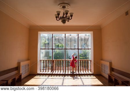 Russian Ballet School Concept Of Little Thin Girl Dancing Near Window In Hall With Street Behind Win