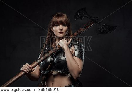 Atmospheric Portrait Of Scandinavian Amazon With Brown Hairs Dressed In Light Armour Holding Two Han
