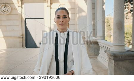 Young Posh Elegant Woman In Suit Confidently Walking Along City Park With Old Beautiful Architecture