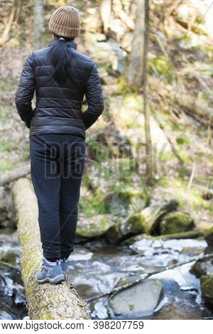 A Woman Standing On A Log Over A Flowing Stream Covered In Ice And Snow In Deans Ravine In Falls Vil