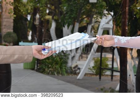 Wo Female Hands Pass Each Other A Medical Mask In A Park On The Street. High Quality Photo