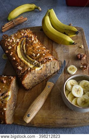 Wholegrain Banana Bread Freshly Sliced On A Cutting Board, With Banana, Cinnamon And Nuts. Bake Shop