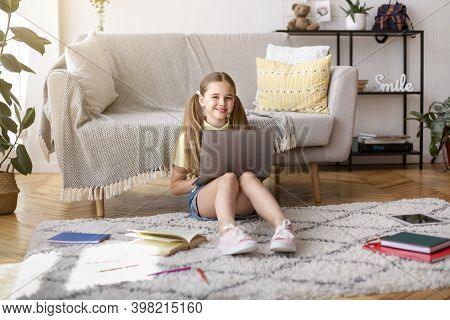 Education And Leisure Concept. Portrait Of Smiling Female Teenager Girl Sitting On The Floor Carpet,