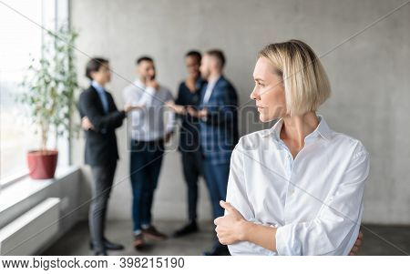 Male Coworkers Whispering Behind Back Of Unhappy Businesswoman Spreading Rumors And Gossips Standing