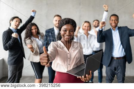 African Businesswoman With Laptop Gesturing Thumbs Up Standing With Joyful Colleagues In Modern Offi