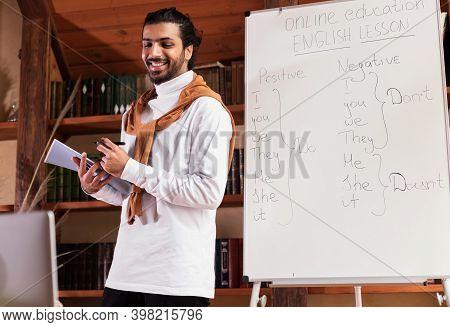 Distance Teaching. Cheerful Indian Teacher Having English Class Online Talking To Laptop Webcam Stan