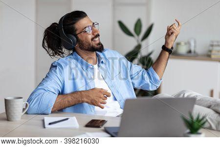 Be Yourself. Joyful Weatern Freelancer Guy Listening Music In Headphones And Playing Virtual Guitar,