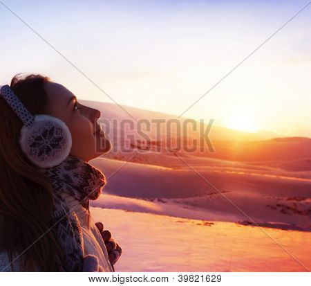 Photo of pretty woman walking in snowy mountains, side view of cute girl looking up, closeup portrait of female wearing warm winter earmuff, red sunset, wintertime sports, trekking and hiking concept