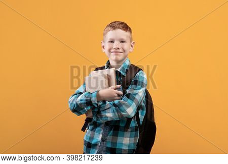 Cheerful Schoolboy With Backpack Holding Heap Of Books, Yellow Studio Background, Copy Space. Happy
