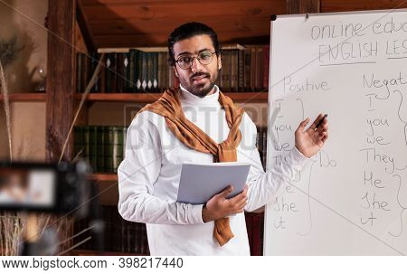 E-teaching. Indian Teacher Guy Teaching Online Standing Near Blackboard Explaining English Language