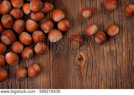 Hazelnut Harvest. Lots Of Hazelnuts On A Wooden Background In Rustic Style. Hazelnuts Scattered On T