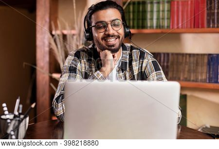 Cheerful Arab Student Guy Watching Educational Video Lecture Online On Laptop Learning Distantly Sit