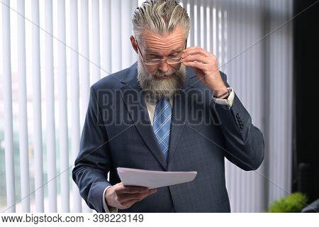 The Mature Gray-haired Company Executive Examines The Reports And Shakes His Head In Accusation. The