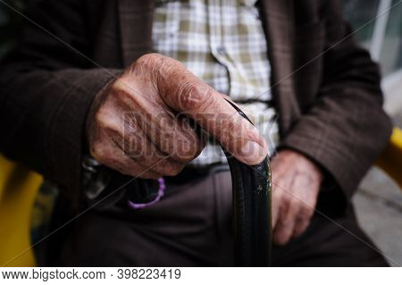 An Elderly Unrecognizable Man Sits On A Chair With A Stick In His Hands. Wrinkled Hands Close Up. Co