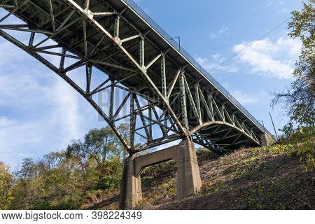 Hillside With Concrete Supports Of An Overhead Arch Bridge, Fall Season With Blue Sky, Horizontal As