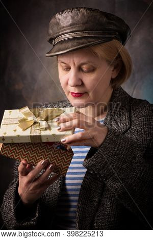 The Woman With A Gift Box. Festive And Joyful Mood From Happiness Anticipation. Cap And Jacket.