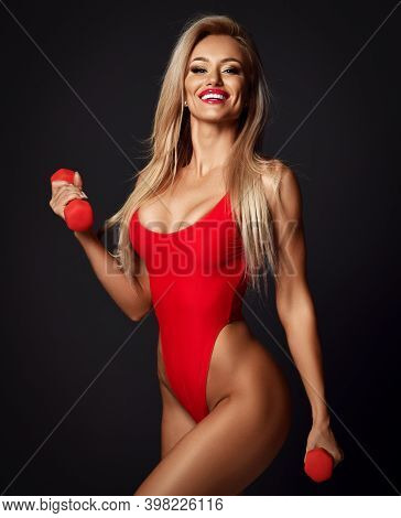 Sexy Smiling Fitness Woman In Red Bikini With Perfect Boobs And Buttocks Standing With Dumbbels In H