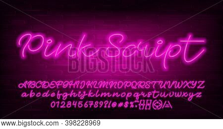 Pink Script Alphabet Font. Pink Neon Light Letters, Numbers And Symbols. Brick Wall Background. Stoc