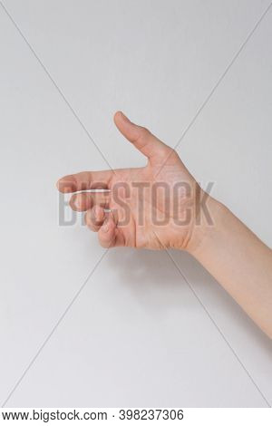 Close Up Hand Holding Something Like A Bottle Or Can Isolated On White Background.
