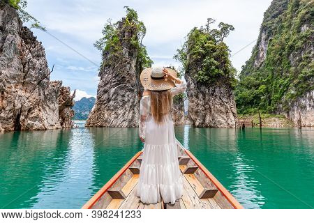 Back View Of Young Female Tourist In Dress And Hat At Longtail Boat Exploring Lake With Limestone Cl