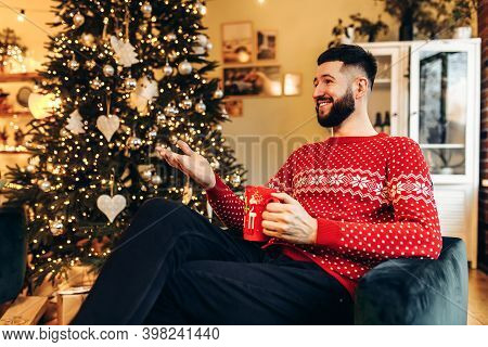 Young Man With A Beard, In A Red Sweater, Sits On The Sofa With A Cup And Drinks Tea At Home Near A