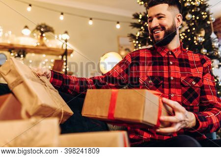 Young Man Opening Christmas Gifts At Home Against The Background Of A Decorated Christmas Tree, Merr