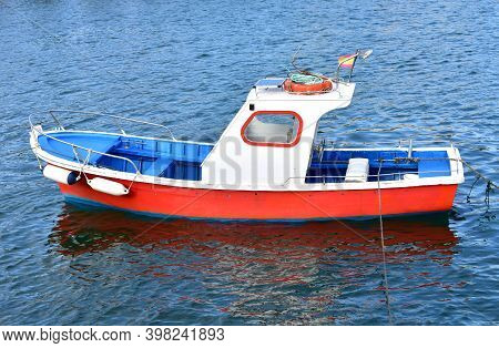 Red White And Blue Traditional Wooden Galician Fishing Boat Moored In A Harbor. Galicia, Spain.